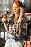 Ritratto della commessa attraente con capelli biondi lunghi e vetri gialli nel deposito di miglioramento domestico con un trapano Immagine Stock