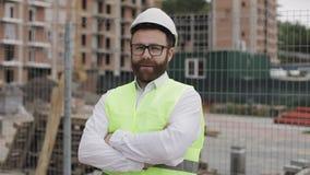 Ritratto della condizione dell'uomo dell'architetto sul cantiere con le mani attraversate che esaminano la macchina fotografica F archivi video