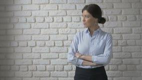 Ritratto della donna abbastanza sexy che esamina macchina fotografica Priorità bassa bianca del muro di mattoni archivi video