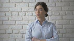 Ritratto della donna abbastanza sexy che esamina macchina fotografica Priorità bassa bianca del muro di mattoni stock footage