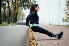 Ritratto della donna in abiti sportivi, facente esercizio di spinta-UPS di forma fisica al parco di caduta, all'aperto Immagini Stock