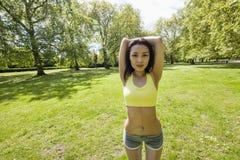 Ritratto della donna adatta dei giovani che allunga al parco Immagini Stock