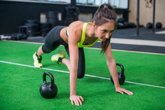 Ritratto della donna adatta dei giovani che fa gli esercizi di forma fisica delle gambe e dell'ABS in palestra Fotografie Stock Libere da Diritti