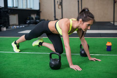 Ritratto della donna adatta dei giovani che fa gli esercizi di forma fisica delle gambe e dell'ABS in palestra Immagine Stock Libera da Diritti