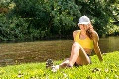 Ritratto della donna adatta dei giovani che si siede sull'erba Fotografia Stock