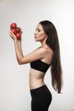 Ritratto della donna adatta dei giovani che tiene i pomodori rossi lucidi Immagine Stock