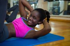 Ritratto della donna adatta sorridente che fa allungando esercizio sulla stuoia Immagine Stock Libera da Diritti