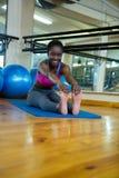 Ritratto della donna adatta sorridente che fa allungando esercizio sulla stuoia Fotografia Stock
