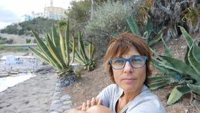 Ritratto della donna adulta con gli occhiali ed i capelli rossi Oceano d'ondeggiamento defocused nei precedenti video d archivio