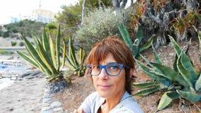 Ritratto della donna adulta con gli occhiali ed i capelli rossi Oceano d'ondeggiamento defocused nei precedenti stock footage