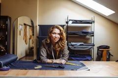 Ritratto della donna adulta piacevole del sarto da donna all'officina dei sarti fotografia stock libera da diritti