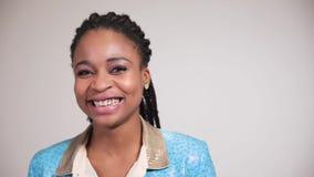 Ritratto della donna afroamericana che esamina largamente macchina fotografica ed i sorrisi archivi video