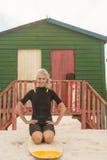 Ritratto della donna allegra che si inginocchia sul surf contro la capanna Fotografia Stock