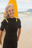 Ritratto della donna allegra che sta con il surf sulla riva Fotografie Stock Libere da Diritti