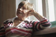 Ritratto della donna anziana felice a casa vicino alla finestra Immagine Stock
