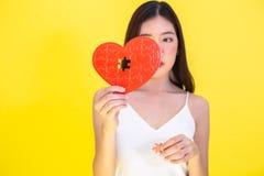 Ritratto della donna asiatica attraente che tiene il puzzle rosso della carta del cuore su fondo rosa-rosso fotografia stock
