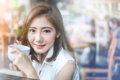 Ritratto della donna asiatica che sorride e che tiene tazza di caffè Immagini Stock