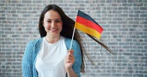 Ritratto della donna attraente che tiene bandiera tedesca sul fondo del muro di mattoni archivi video