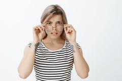 Ritratto della donna attraente incerta preoccupata che ritiene intensa e nervosa, aggrottante le sopracciglia, decollante i vetri Fotografia Stock Libera da Diritti