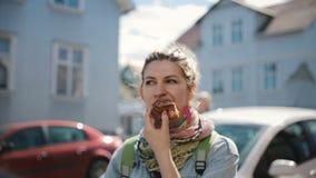 Ritratto della donna attraente sveglia che sta sulla via e che mangia il panino al forno Femminili affamati prendono una rottura  archivi video