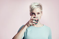 Ritratto della donna bionda con bicchiere d'acqua, fondo luminoso dei capelli di scarsità Fotografia Stock