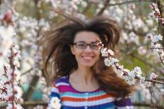 Ritratto della donna castana caucasica sorridente nel giardino del fiore di primavera immagini stock libere da diritti