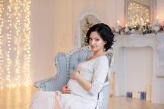 Ritratto della donna castana incinta in un vestito bianco nel inte Immagini Stock