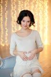 Ritratto della donna castana incinta in un vestito bianco nel inte Immagine Stock