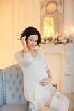 Ritratto della donna castana incinta in un vestito bianco nel inte Fotografie Stock