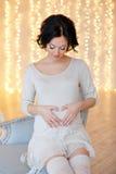 Ritratto della donna castana incinta in un vestito bianco nel inte Immagine Stock Libera da Diritti