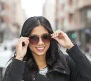 Ritratto della donna casuale attraente sorridente con gli occhiali da sole. Fotografie Stock Libere da Diritti