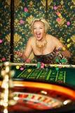 Ritratto della donna che gioca roulette al casinò Immagine Stock