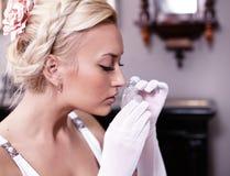 Ritratto della donna che sente l'odore di una bottiglia di profumo Fotografia Stock