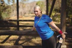 Ritratto della donna che si esercita durante la corsa ad ostacoli Fotografia Stock