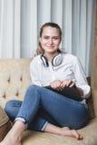 Ritratto della donna che si siede sul sofà e che ascolta la musica Fotografie Stock