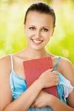Ritratto della donna che tiene un libro a Immagini Stock