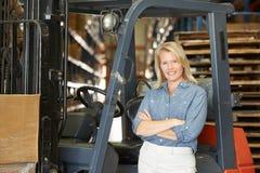 Ritratto della donna con il carrello elevatore a forcale in magazzino Fotografia Stock