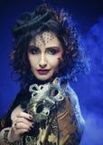Ritratto della donna con la maschera artistica della tenuta di trucco Fotografia Stock