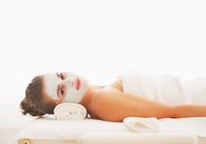 Ritratto della donna con la maschera di ravvivamento sul fronte che mette sulla tavola di massaggio Fotografia Stock