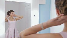 Ritratto della donna con trucco che esamina la sua riflessione in specchio, capelli di riparazione video d archivio