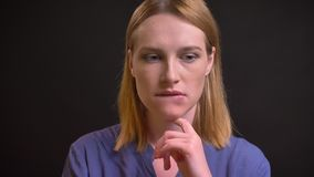 Ritratto della donna convenzionale-vestita che tocca meditatamente il suo mento e che ottiene una comprensione su fondo nero archivi video