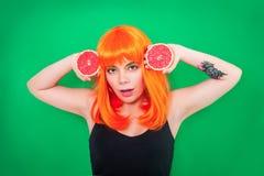 Ritratto della donna dai capelli rossi con pompelmi in primo piano dello studio Fotografia Stock