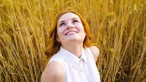 Ritratto della donna dai capelli rossi felice che cerca nel cielo che si siede nel giacimento di grano video d archivio
