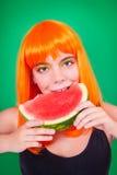 Ritratto della donna dai capelli rossi in primo piano dello studio con l'anguria immagini stock