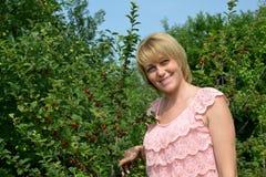 Ritratto della donna degli anni medii nel frutteto di ciliegia Immagine Stock