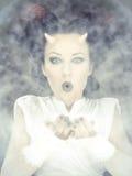 Ritratto della donna del diavolo che soffia una polvere bianca fotografia stock