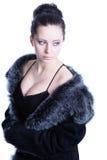 Bello castana con decollete in pelliccia nera di lusso di colore che guarda via Fotografie Stock