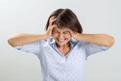 Ritratto della donna deludente, degli occhi chiusi e delle orecchie, gridanti nella disperazione, immagine della casa su un fondo Fotografia Stock Libera da Diritti