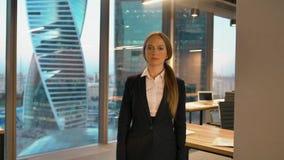 Ritratto della donna di affari allegra allegro nella posa convenzionale sulla macchina fotografica che dà come il segno con il po archivi video