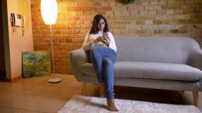 Ritratto della donna di affari castana attraente che si siede sul sofà e che guarda con la considerazione nello smartphone a casa archivi video